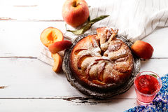 Sweet pie with fresh summer peaches. On white wooden distressed background with a glass of rose water. Harvest time concept. Composition with copy space taken Royalty Free Stock Photography
