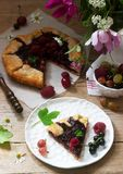 Sweet pie galette with juicy berry filling, berries and wild flowers on a wooden background. Rustic style. stock photo