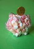 Sweet Piggy Bank. Piggy bank full of sweets with a chocolate coin sitting on the top of it Stock Photo