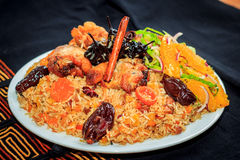 Sweet pilaf with chicken, prunes, dried apricots, spiced pear and cinnamon sticks, decorated with orange salad. Royalty Free Stock Photo