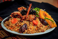Sweet pilaf with chicken, prunes, dried apricots, spiced pear and cinnamon sticks, decorated with orange salad. Stock Photo