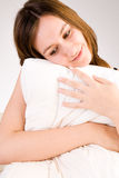 Sweet pillow. Young woman portrait in the studio on a white background royalty free stock image