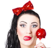 Sweet pin-up girl eating a candy toffee apple Stock Photos