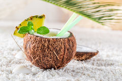 Sweet pinacolada in coconut with pineapple and mint leaves Royalty Free Stock Images