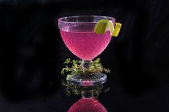Sweet pink cocktail with lemon royalty free stock photography