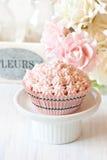 Pink cupcake. Sweet pink cupcake on a cake stand Royalty Free Stock Photos