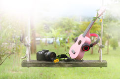 Sweet pink headphones, ukulele music, camera on wooden swing. Royalty Free Stock Image