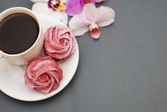 Sweet Pink Meringues and Cup of Coffee on Blue Gray background with Orchid Flowers. Spring Background with copy space. Breakfast. stock photo