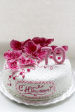 Sweet pink orchids white anniversary cake closeup Stock Photography
