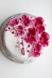 Sweet pink orchids white anniversary cake closeup Stock Photo