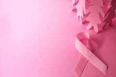 Sweet pink ribbon shape with the girl paper doll on pink backgro Royalty Free Stock Photos