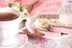 A sweet pink rose cup cake with tea pot and cup on the table in the english garden royalty free stock photography