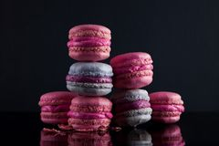 Sweet pink, violet french macaroon cookies on black background stock photos