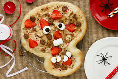 Sweet pizza in the form of funny skull to treat kids at Hallowee Stock Photography