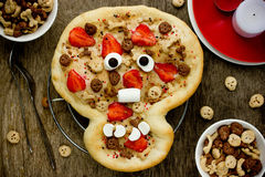 Sweet pizza in the form of funny skull to treat kids at Hallowee Stock Photos