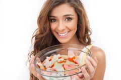 Sweet plate. Beautiful young women holding a plate full of candi Stock Photo