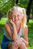 Sweet, playful blond girl sitting in the green garden and backin Royalty Free Stock Photography
