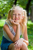 Sweet, playful blond girl sitting in the green garden and backin Stock Image
