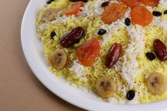 Sweet plov or pilaf with dried fruits and clarified butter on big white plate: eastern cuisine. Close up Stock Images
