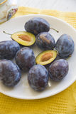 Sweet plums on yellow tablecloth Stock Photography
