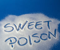 SWEET POISON written with sugar. Sugar on a blue background with warning message SWEET POISON written on it. Health concept. Diabetes hazard Stock Photo