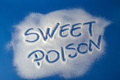 SWEET POISON written with sugar. Sugar on a blue background with warning message SWEET POISON written on it. Health concept. Diabetes hazard Stock Photography