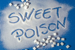 SWEET POISON written with sugar. Sugar on a blue background with warning message SWEET POISON written on it. Health concept. Diabetes hazard Royalty Free Stock Photography