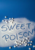 SWEET POISON written with sugar. Sugar on a blue background with warning message SWEET POISON written on it. Health concept. Diabetes hazard Stock Image