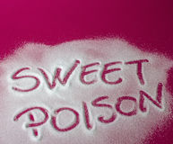 SWEET POISON written with sugar. Sugar on a red background with warning message SWEET POISON written on it. Health concept. Diabetes hazard Royalty Free Stock Photography