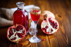 Sweet pomegranate alcoholic cordial in the decanter with a glass Royalty Free Stock Photos