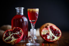 Sweet pomegranate alcoholic cordial in the decanter with a glass Royalty Free Stock Photo