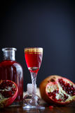 Sweet pomegranate alcoholic cordial in the decanter with a glass Stock Photos