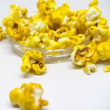 Sweet popcorn  on white background. The Sweet popcorn  on white background. Popcorn, or pop-corn, is a variety of corn kernel, which forcefully expands and puffs Stock Photography