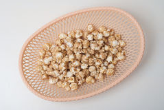 sweet popcorn in a wicker basket on a light background, Stock Photos