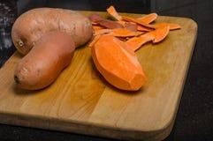 Sweet potaoes peeled on cutting board Stock Photos