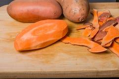 Sweet potaoes peeled on cutting board Stock Photo