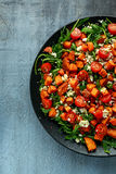 Sweet potato, carrots, cherry tomatoes and wild rocket salad with feta cheese served in black plate.  Royalty Free Stock Photo
