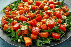 Sweet potato, carrots, cherry tomatoes and wild rocket salad with feta cheese served in black plate.  Stock Photography