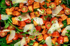 Sweet potato, carrots, cherry tomatoes and wild rocket salad with feta cheese served in black plate.  Stock Photos