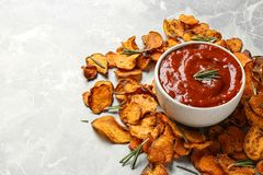 Sweet potato chips and bowl of sauce on grey. Background. Space for text royalty free stock image