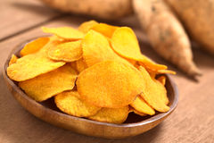 Sweet Potato Chips. Crispy Peruvian sweet potato chips on wooden plate with sweet potatoes in the back (Selective Focus, Focus one third into the sweet potato stock photo