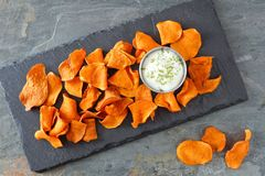Sweet potato chips with dip, above view on slate Royalty Free Stock Images