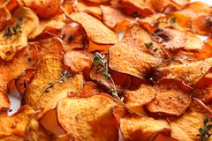 Sweet potato chips with herbs as background. Closeup stock images