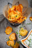 Sweet potato chips. Homemade sweet potato chips with fresh thyme Stock Photos