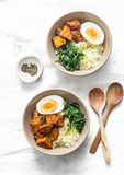 Sweet potato, couscous, spinach, egg buddha bowl on light background, top view. Vegetarian food stock photo