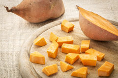 Sweet potato diced. Sweet potato cut and diced on a cutting board Stock Photos