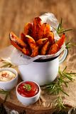 Sweet potato french fries seasoned herbs and sea salt in enamel mug and spicy dips on a wooden table. Delicious and healthy vegetarian snack stock image