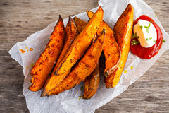 Sweet potato fries in paper wrap executed in metal serving basket with fresh cream dip souce on old wooden table Stock Photos