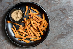 Sweet Potato Fries with Spiced Salt. Black rustic dish, top view, over slate Stock Photos