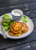Sweet potato pancakes and fresh spinach. On a dark wooden background royalty free stock images